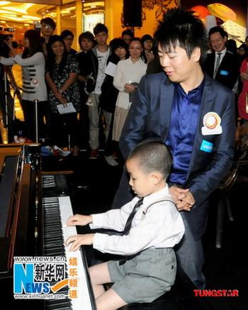 郎朗出席慈善演奏会 为幼童踩琴板惹哄堂大笑